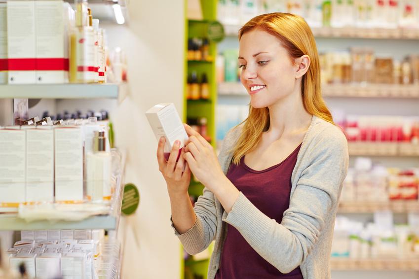 Frau hält Produkt in der Drogerie in der Hand
